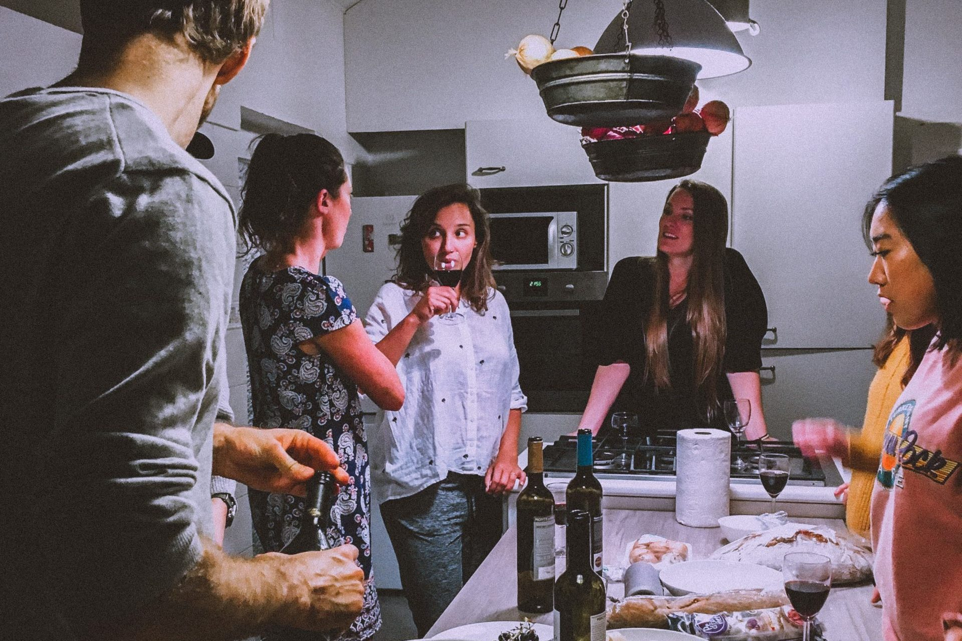 Group of friends gathering in a kitchen.