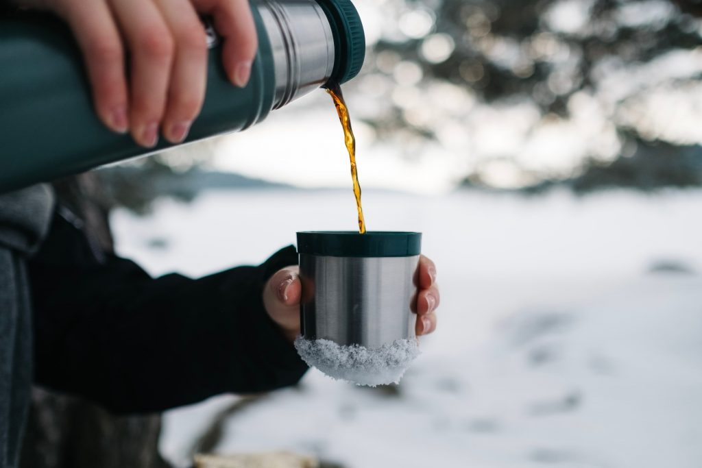 Guy pours tea into thermos during winter during a winter picnic outdoors.