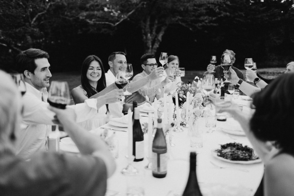 Big dinner party cheersing at the dinner table.